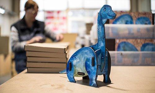Eine Stiftebox in Form eines blauen Dinosauriers.